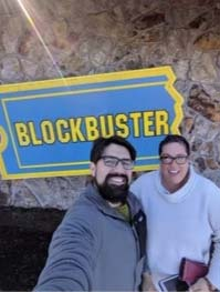 2 people in front of Blockbuster Store