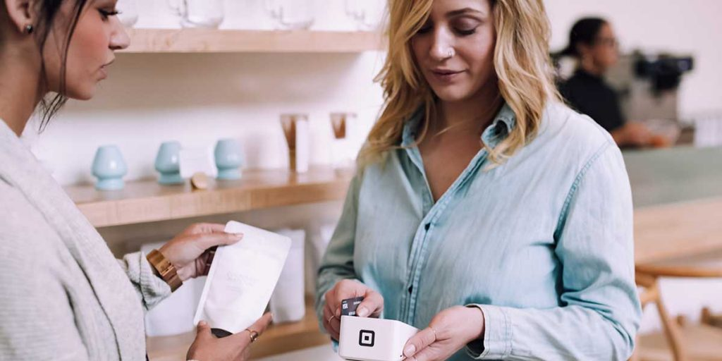 Woman Using Square for Credit card Transaction